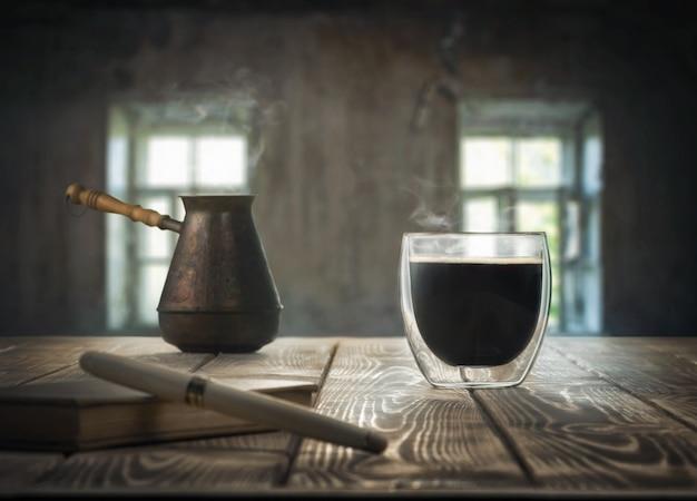 Um copo de café, uma caneta e um caderno em cima da mesa