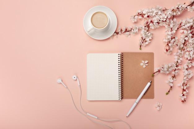 Um copo de cappuccino branco com flores de sakura, caderno, fones de ouvido, caneta