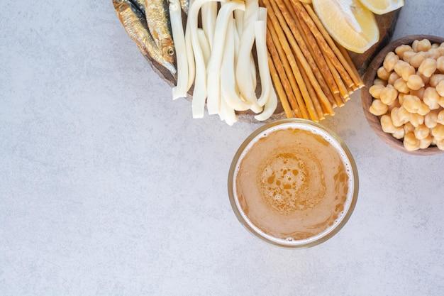 Um copo de cerveja com ervilhas e peixe no prato de madeira