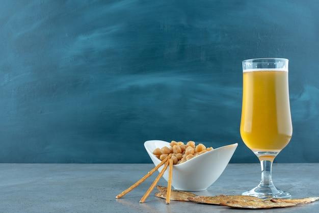 Um copo de cerveja com ervilhas e peixes em fundo cinza. foto de alta qualidade