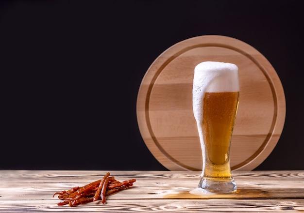Um copo de cerveja com espuma e um petisco de palitos de peixe seco