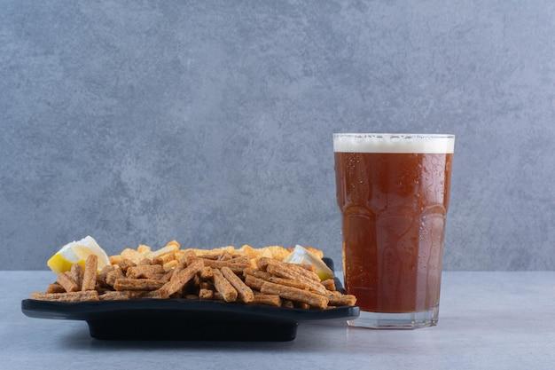 Um copo de cerveja com peixe e palitos de pão na superfície cinza