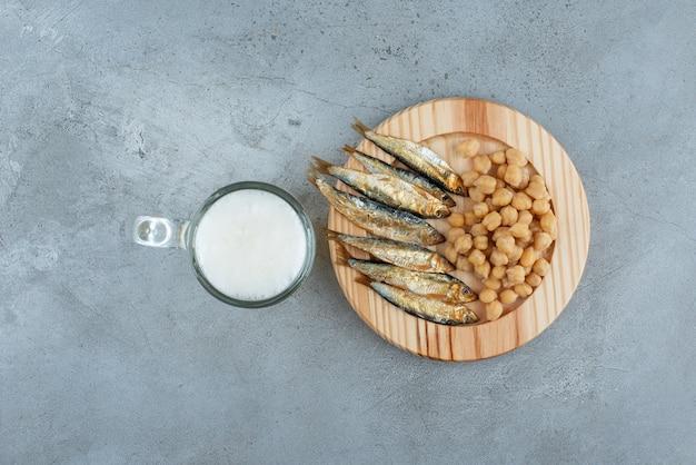 Um copo de cerveja com prato de madeira de peixe e ervilhas. foto de alta qualidade