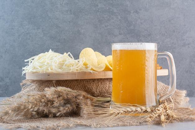 Um copo de cerveja com trigo e batata frita no feno.