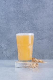 Um copo de cerveja com trigo na superfície branca