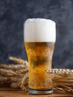 Um copo de cerveja contra uma parede escura