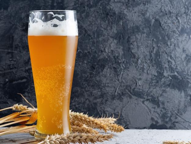 Um copo de cerveja de trigo em um fundo escuro de concreto e espigas de trigo
