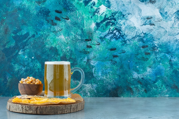 Um copo de cerveja e aperitivos a bordo em azul.