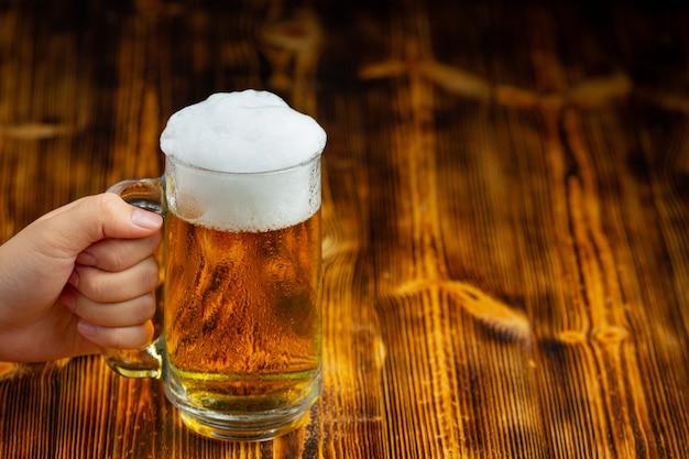 Um copo de cerveja é colocado no chão de madeira.