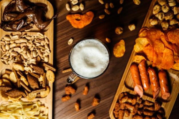 Um copo de cerveja e vários petiscos na mesa para ele