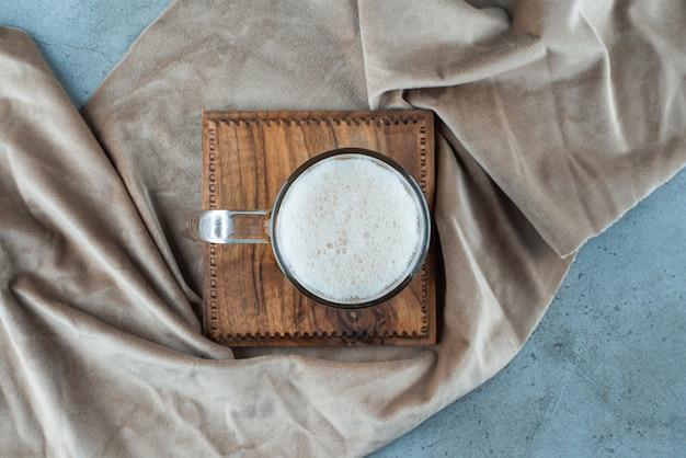 Um copo de cerveja em uma placa sobre uma toalha, na mesa azul.