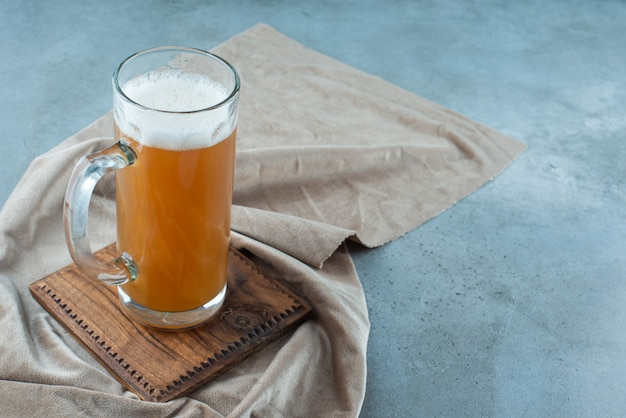 Um copo de cerveja em uma placa sobre uma toalha, sobre o fundo azul.
