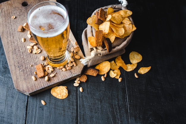 Um copo de cerveja fresca com batata chips e amendoins em fundo preto