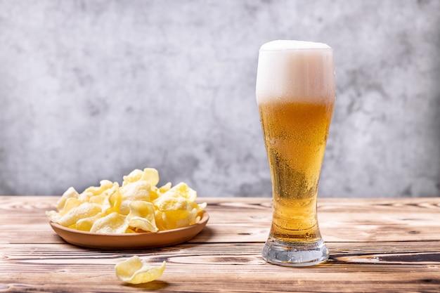 Um copo de cerveja gelada com batatas fritas