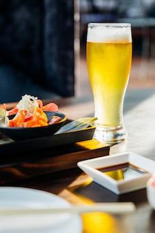 Um copo de cerveja gelada com espuma na mesa de madeira com borrão refeição em primeiro plano