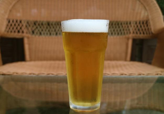 Um copo de cerveja gelada isolado na mesa com uma cadeira vazia embaçada