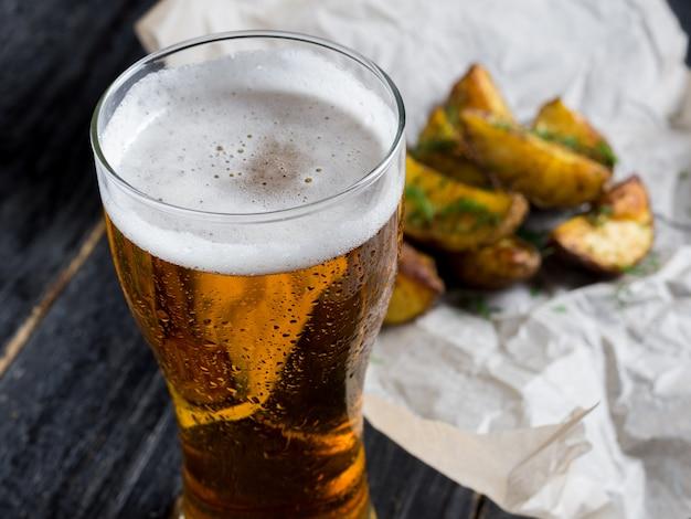 Um copo de cerveja light com um lanche em forma de batatas rústicas com endro sobre um fundo escuro de madeira