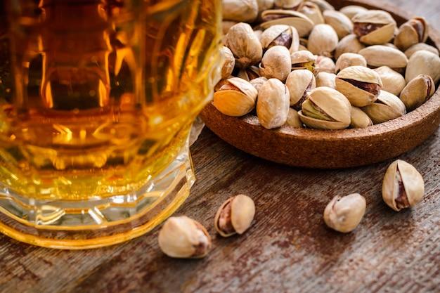Um copo de cerveja light e um punhado de pistachios em uma mesa de madeira