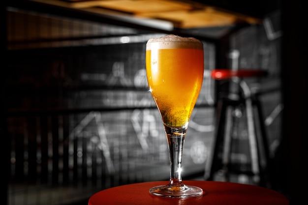 Um copo de cerveja loira em uma perna magra em um bar.