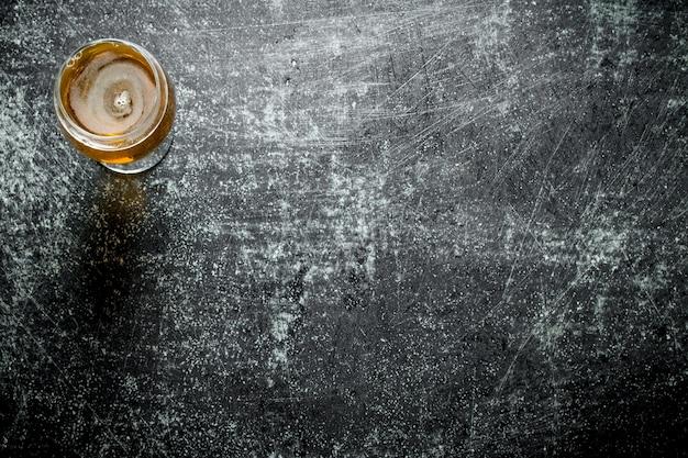 Um copo de cerveja. na mesa rústica preta