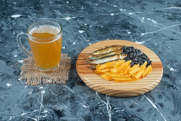 Um copo de cerveja na textura e aperitivos na placa de madeira, sobre o fundo azul.