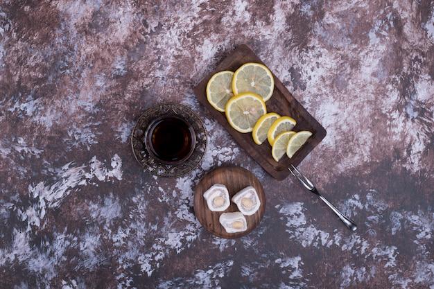 Um copo de chá com lokum e limão cortado