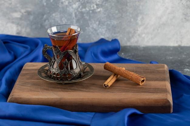 Um copo de chá com paus de canela em uma tábua de madeira.