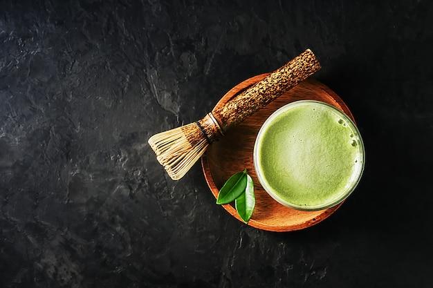 Um copo de chá matcha com leite em um fundo escuro de concreto