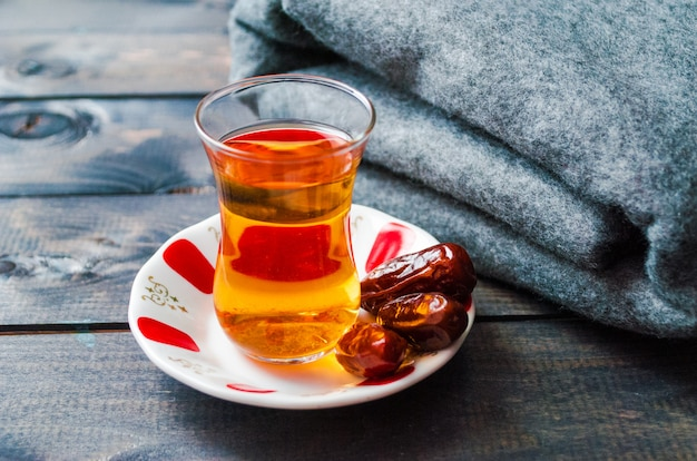 Um copo de chá preto e tâmaras em um pires