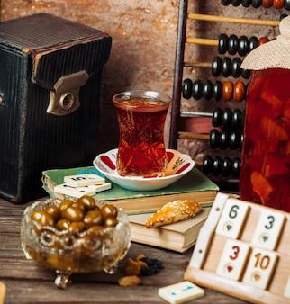 Um copo de chá preto e tâmaras frescas em uma mesa de jogo à tarde.