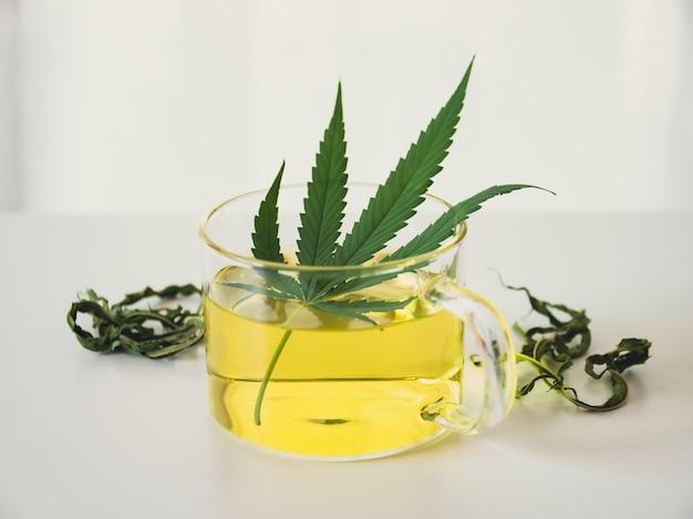 Um copo de chá quente de maconha na mesa. chá de ervas de cannabis com folhas secas.
