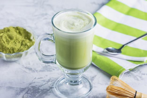 Um copo de chá verde com leite fresco. receita incomum com chá matcha e leite de soja. uma bebida vegetariana saudável