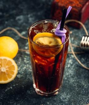 Um copo de coca-cola com cubos de gelo e uma fatia de limão no fundo cinza