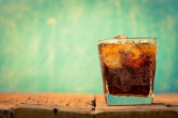 Um copo de coca-cola com cubos de gelo