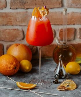 Um copo de cocktail vermelho alaranjado com fatias de laranja na parte superior.