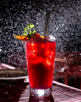 Um copo de cocktail vermelho decorado com fatias de laranja em fundo escuro com luz