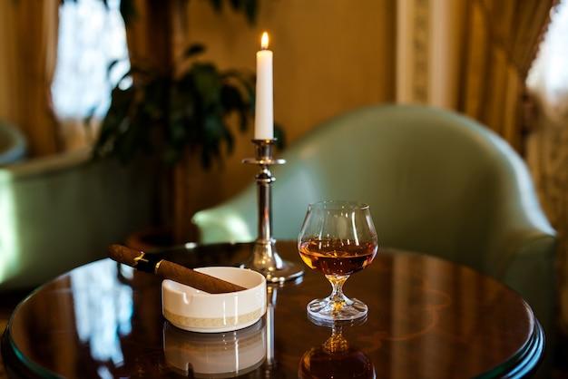 Um copo de conhaque, charuto e velas sobre uma mesa de madeira.