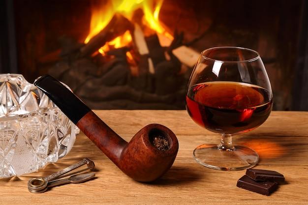 Um copo de conhaque, chocolate e cachimbo de tabaco na mesa de carvalho no fundo de uma lareira a lenha