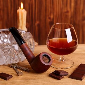 Um copo de conhaque, chocolate e cachimbo na mesa de carvalho