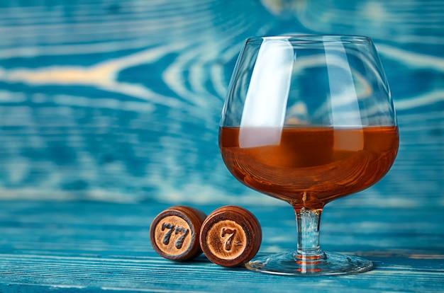 Um copo de conhaque e barris de madeira com o número sete em uma mesa de madeira azul