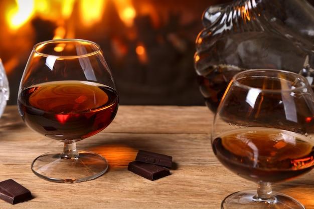 Um copo de conhaque e chocolate na mesa de carvalho no fundo de uma lareira a lenha