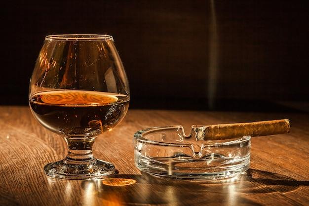 Um copo de conhaque e um charuto na mesa de madeira.