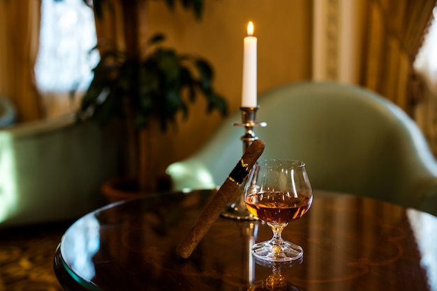 Um copo de conhaque e um charuto na mesa.