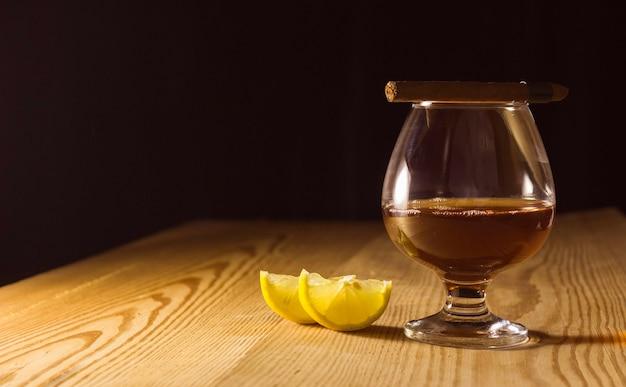 Um copo de conhaque em uma mesa de madeira, uma rodela de limão e um charuto em um copo. espaço livre para texto ao lado.