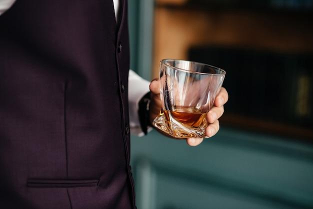Um copo de conhaque na mão masculina
