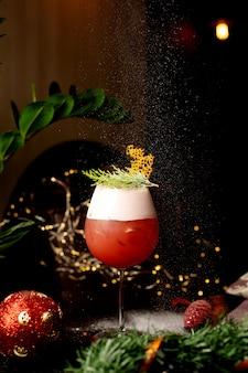 Um copo de coquetel cítrico decorado com folhas de pinheiro na véspera de natal