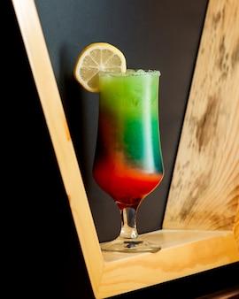 Um copo de coquetel ombre com cores verde e laranja, coberto com limão