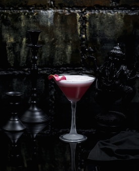 Um copo de cosmopolita rosa em fundo escuro