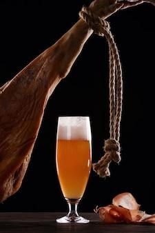 Um copo de espuma de cerveja light, perna, presunto de parma. sobre fundo preto. lugar para logotipo.