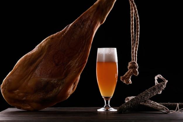 Um copo de espuma de cerveja light, perna, presunto de parma, variedades caras de linguiça. sobre fundo preto. lugar para logotipo.
